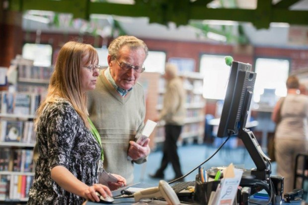 Library staff helping a visitor in Broadstone library, Poole.