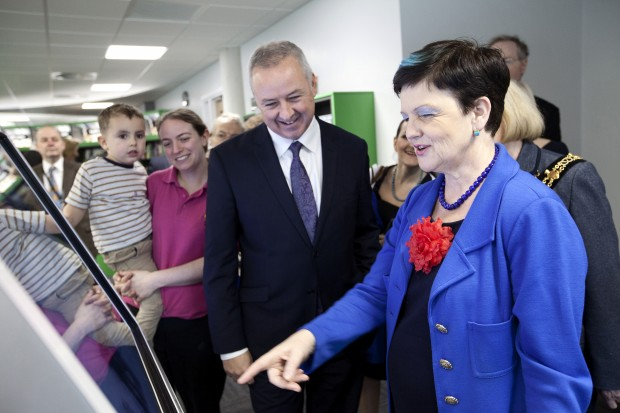 Cllr Ben Adams looks on as Baroness Neville-Rolfe explores the touch screens in the new Stafford library.