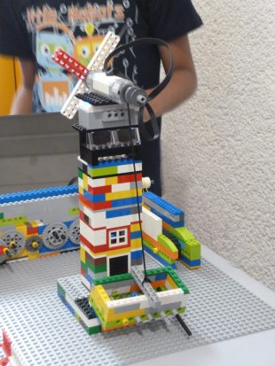 Participant in the Junior LEGO league with their creation. Photo credit: XXX