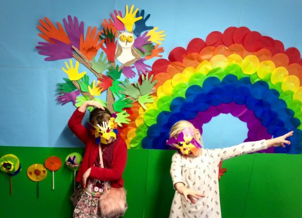 children standing in front of a rainbow artwork