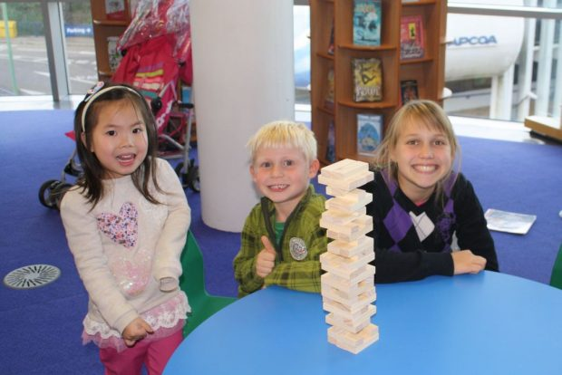 Photo of 3 children playing Jenga in a library.