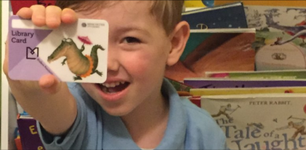 Child with his library card. Photo credit: Manchester libraries