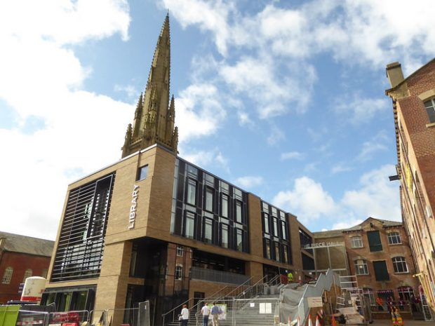 Photo of the outside of a new library with a church spire visible behind