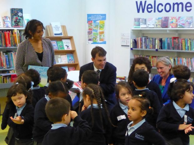 John Glen surrounded by children in Pimlico library. Also just visible are (on the right) author Smriti Prasadam Halls, and on the left, Cllr Jacqui Wilkinson, deputy Cabinet Member for environment and community services, at Westminster Council.