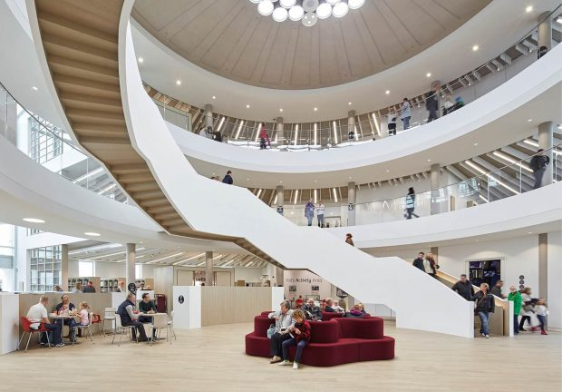 Photo of the inside of a library with a big winding staircase in the centre