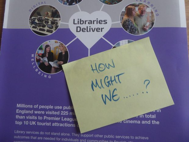 Post-it note saying: How might we?