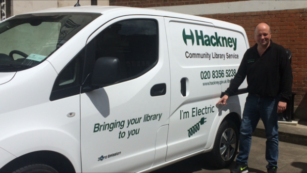 A photo of a man standing beside a new small white van which says 'I'm electric' on the side