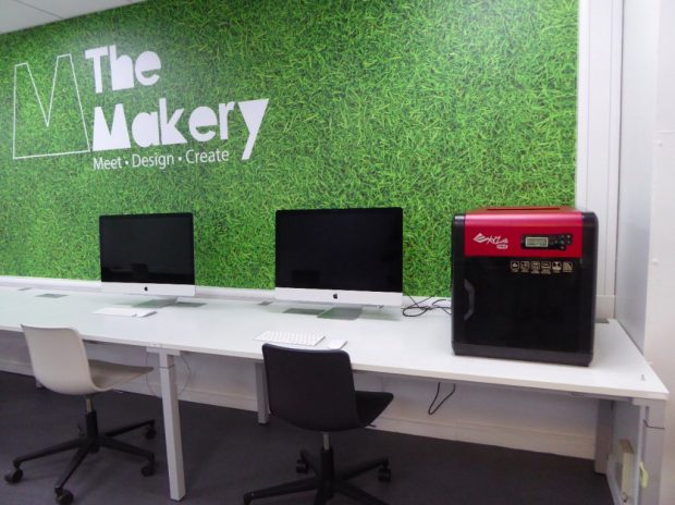Photo of the back wall of the Makery with MAC computers and a 3D printer on a long desk
