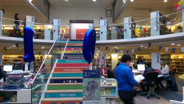 Photo of balloons and bunting inside a library.