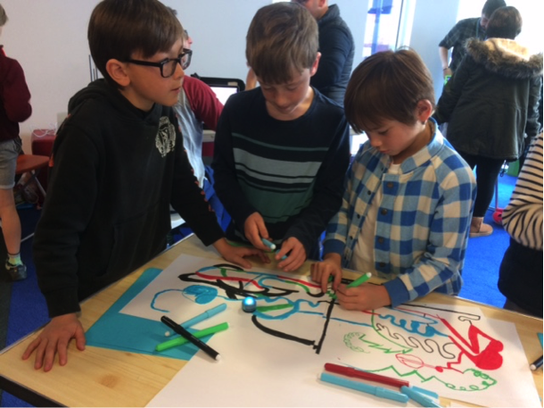 Photo of 3 boys playing using an Ozobot.