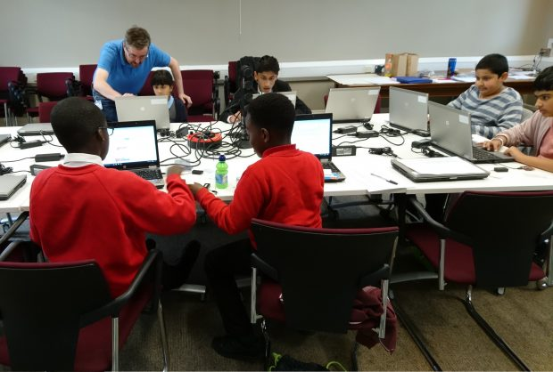 Photo of a group of young people sitting around a table and working on laptops