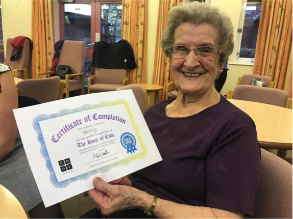 Photo of an older woman holding her certificate