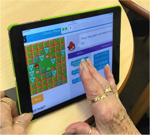 Photo of an older woman using a tablet to code