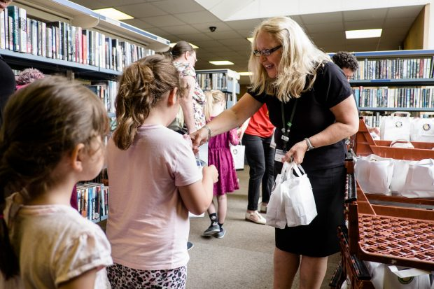 Photo of a lady handing a child a bag containing a packed lunch, in a library