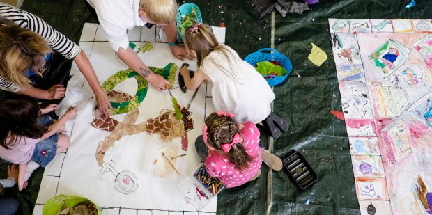 Photo of some children painting on large pieces of paper on the floor
