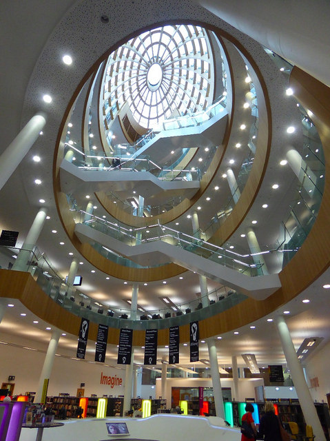 Photo of the inside of a library looking up from the ground floor to the glass dome a few floors above.
