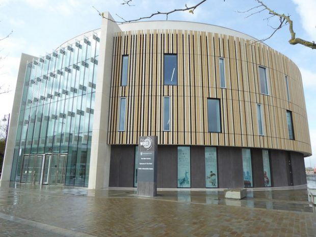 Photo of the outside of a new library with high glass windows and wood cladding.