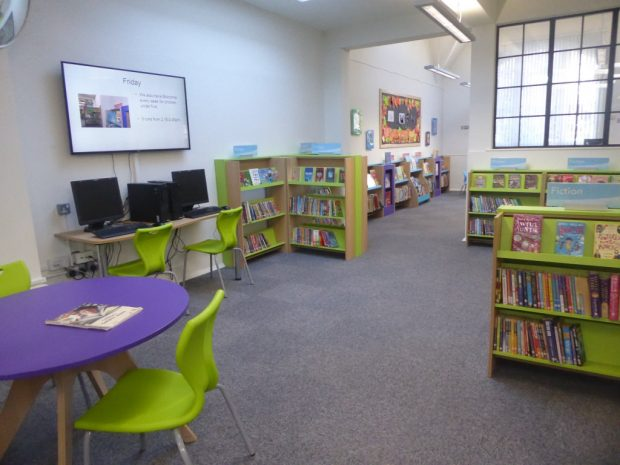 Photo of a children's section in a library which as bright green and purple furniture, lots of low bookcases and 2 computers.