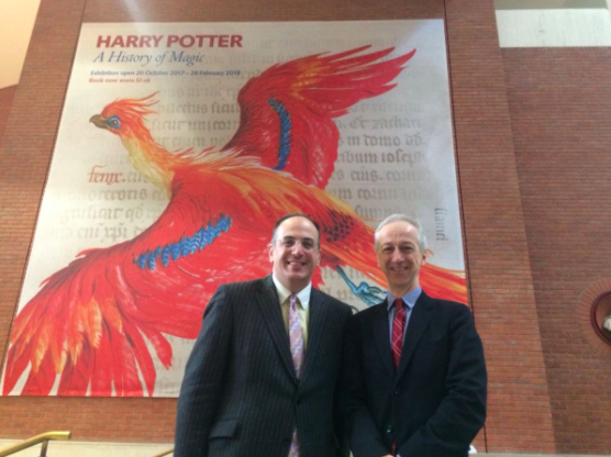 Photo of 2 men standing in front of a Harry Potter: A History of Magic poster