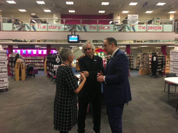 Photo of 3 people talking in a library.
