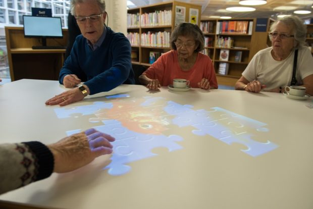 Photo of elderly people sitting around a table with a puzzle projected on it which people are doing.