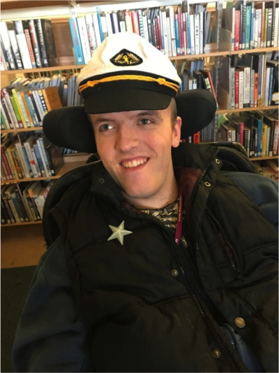 Photo of a young man in a wheelchair with a sailors cap on.