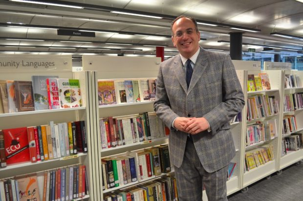 Photo of a man in a grey suit in front of bookcases in a library.
