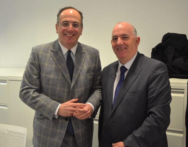 Photo of 2 men standing in a meeting room.
