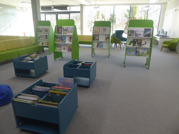 Photo of the inside of a library which is very light with bright green and blue furniture.