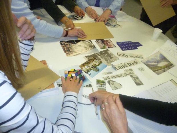 Photo of people moving around photos and newspaper headlines on a table in the library.