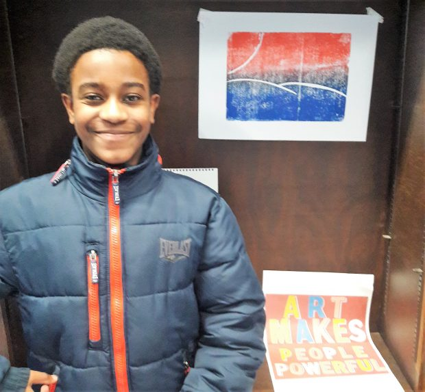 Photo of a smiling boy standing in front of artwork