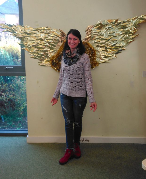 Photo of a woman standing in front of gold angel wings
