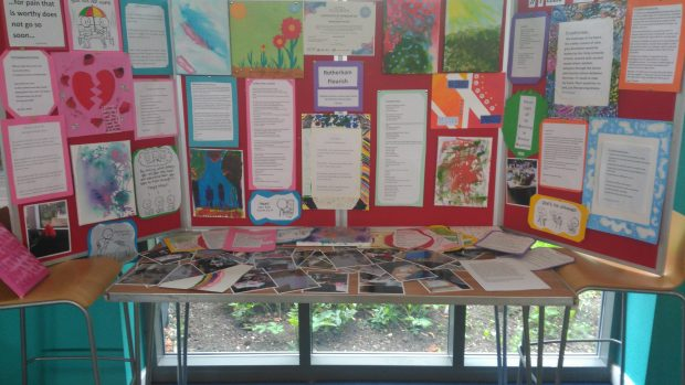 Photo of a table with photos on and 3 display boards with art work and poems on them.