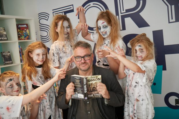 A man holding a book open in front of him with 5 children dressed as ghouls standing around him