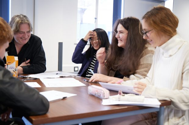 Photo of a group of young people sitting around a table.