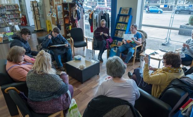 A group of people sitting knitting in a library