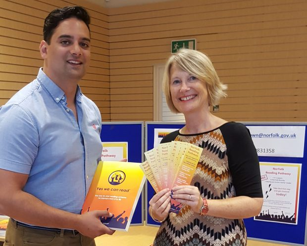 Photo of 2 people holding Norfolk Reading Pathway literature at one of Norfolk's pop-up shops.