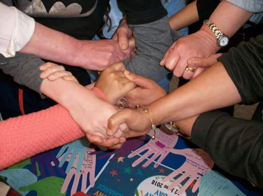 Photo of people holding hands as part of the friendship project in Sheffield.