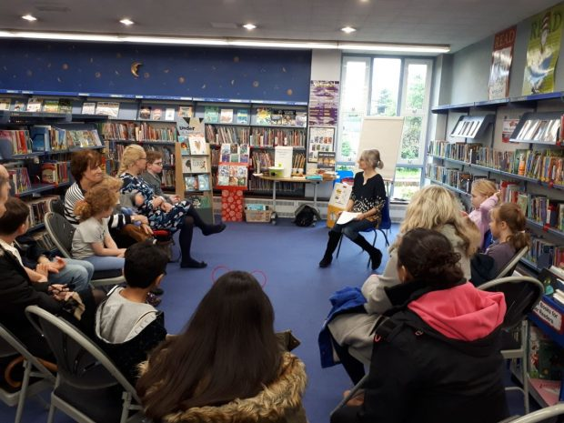 Photo of Helen Moss in Loughton library talking to a group of people sitting around her on chairs.