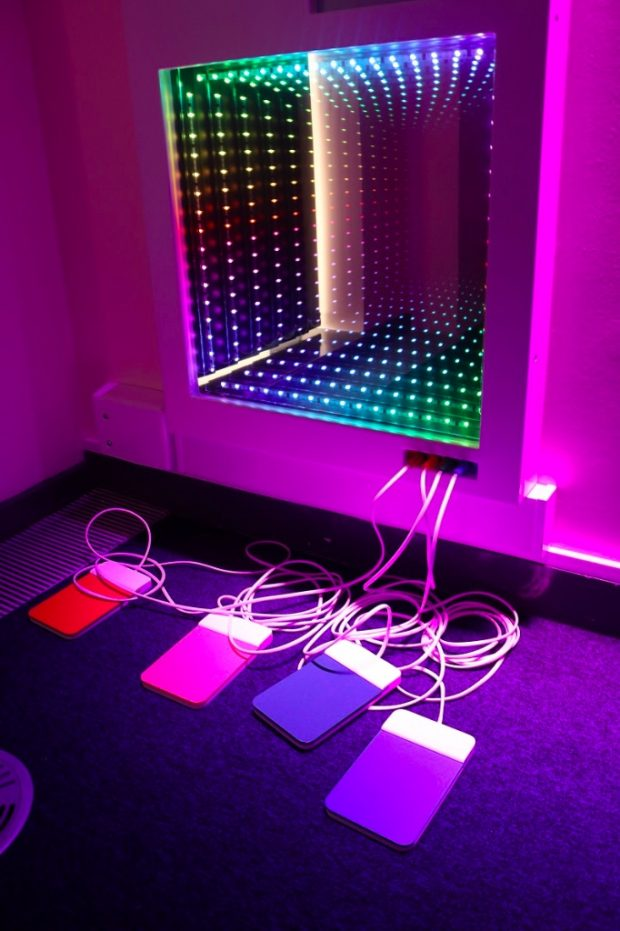 Equipment plugged into the wall in a sensory room which has a wall with lots of light diodes on