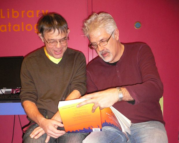 Photo of 2 men reading a Norfolk Reading Pathway book