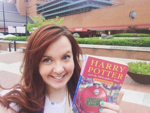 Linda outside the British Library holding a copy of Harry Potter and the Philosopher's stone.