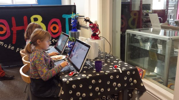 Photo of 2 children sitting at laptops and programming robotic heads which are on the table with them.