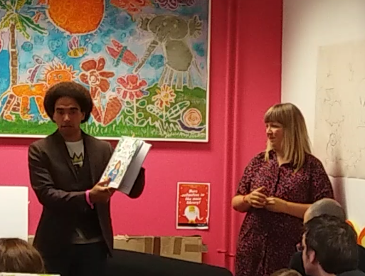 Photo of Joseph Coelho and Fiona Lumbers in Cheltenham children's library. Joseph Coelho is standing in front of people with a book in his hand.