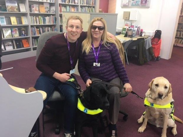 Photo of 2 volunteers with their guide dogs in the library