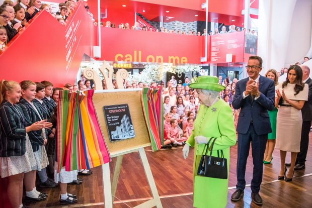 Photo of the Queen unveiling a plaque in Storyhouse. There are lots of school children in the background.