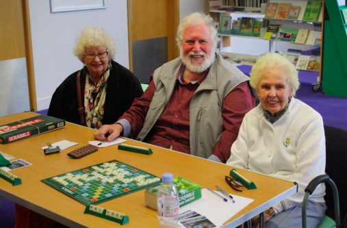 Photo of 3 elderly people playing scrabble in a library