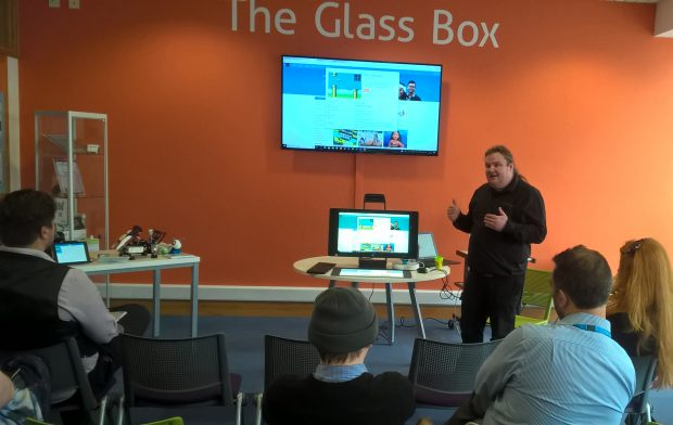 Photo of a group of people watching a presentation showing how to use the HP Sprout
