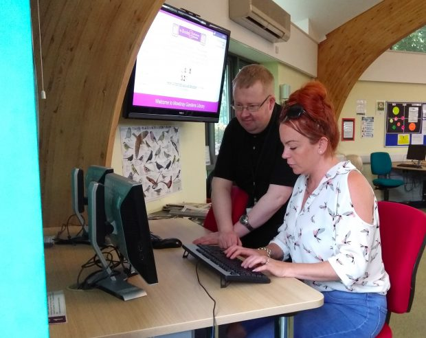 Stephen helping someone get online in Mowbray Gardens library. Photo credit: Chris Gaynor, RMBC