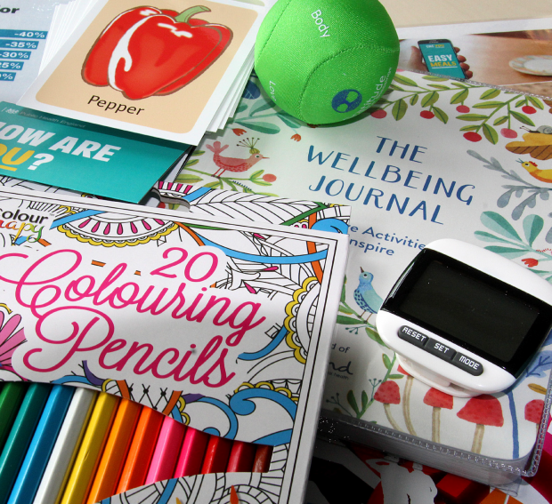 Photo of some of the contents of a wellbeing box including 20 colouring pencils, a squidgy ball, a step counter and a wellbeing journal